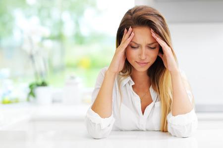 Beeld van jonge trieste vrouw in de keuken