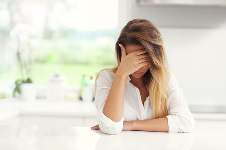 Picture of young sad woman in the kitchen Stockfoto