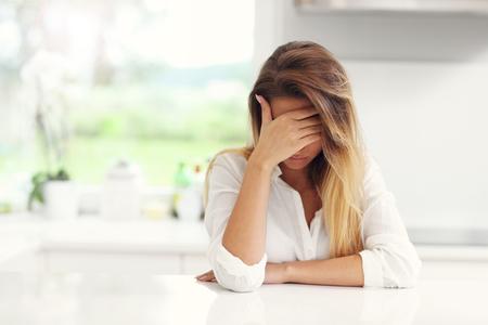 Obrázek mladé smutná žena v kuchyni