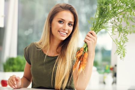carrot: Picture of young woman with fresh carrots in kitchen