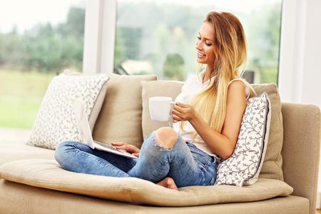 Imagen de la mujer joven en el sofá con el portátil Foto de archivo - 64761230