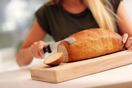 slicing: Picture of woman slicing loaf of bread