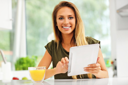 orange juice: Picture of young woman with orange juice and tablet in kitchen