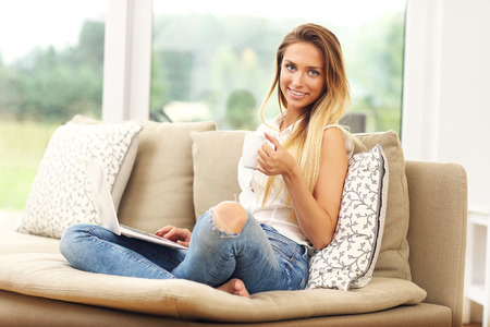 woman laptop: Picture of young woman on couch with laptop