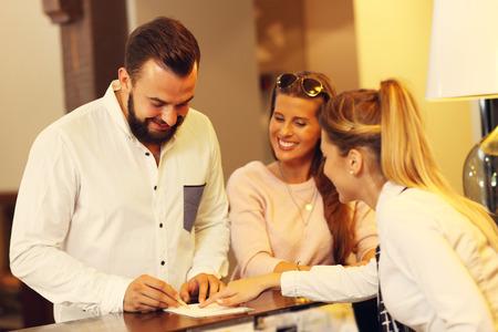 Bild der jungen Geschäftsmann Unterzeichnung Rechnung im Hotel Standard-Bild - 65613817