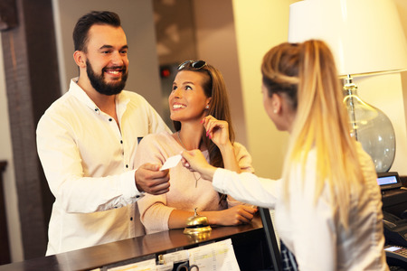 cc: Picture of couple and receptionist at counter in hotel Stock Photo