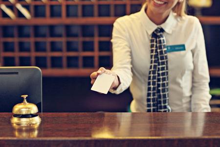 Cuadro de la recepcionista que da la tarjeta llave Foto de archivo - 64761984