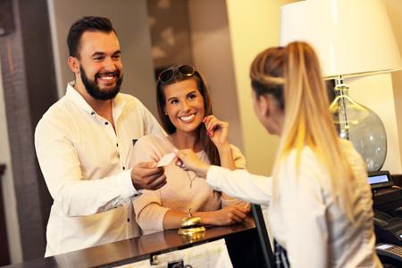 Bild von Paar und Rezeptionistin am Schalter im Hotel Standard-Bild - 65613815