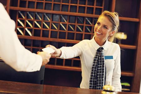 oficinista: Cuadro de la recepcionista que da la tarjeta llave