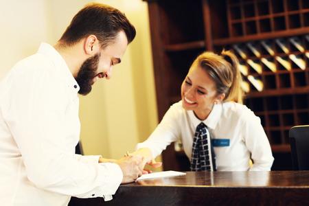 Picture of young businessman signing bill in hotel Stock Photo