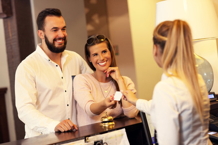 Picture of couple and receptionist at counter in hotel Stockfoto