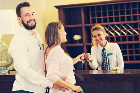 Foto van paar en receptioniste bij teller in hotel Stockfoto