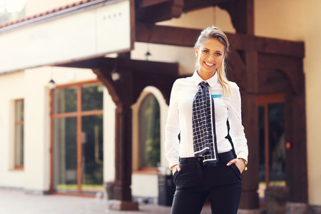 attractive  female: Picture showing manager standing in front of hotel Stock Photo