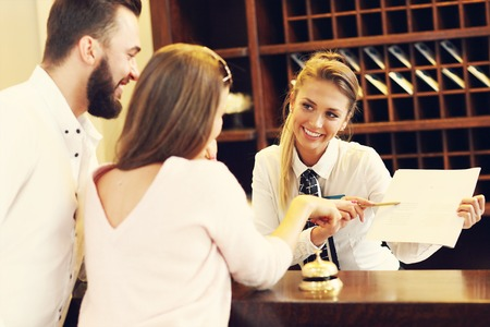 Picture of couple and receptionist at counter in hotel 스톡 콘텐츠