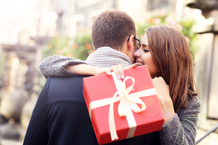 Picture of woman with present giving hug to her man Фото со стока - 64710861
