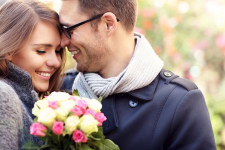 Obrázek ukazuje šťastný pár objímání s květinami ve městě