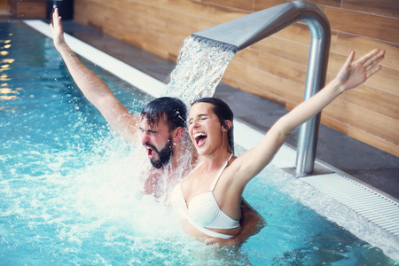 Fotografía de una pareja feliz relajarse en el spa de la piscina