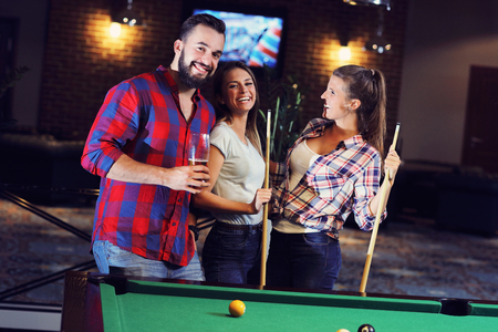 pool table: Picture showing group of friends playing billards