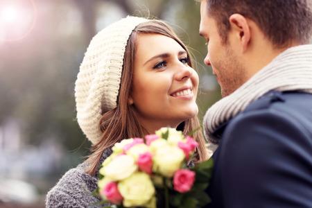 amantes: Imagen que muestra feliz pareja abrazándose con flores en la ciudad Foto de archivo