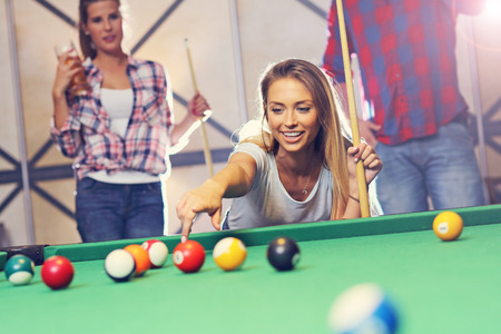 billiards tables: Picture showing group of friends playing billards