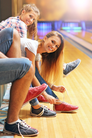 sport shoe: Picture showing friends putting on bowling shoes Stock Photo