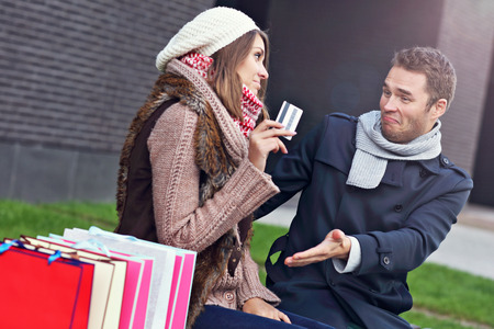 christmas spending: Picture of young man showing disapproval to woman with many shopping bags