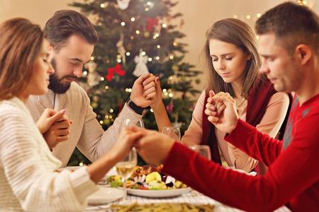 크리스마스 테이블 위에기도하는 친구의 그룹을 보여주는 그림