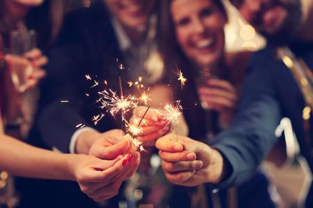 Immagine che mostra un gruppo di amici che hanno divertimento con stelle filanti Archivio Fotografico - 65626404