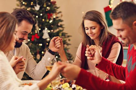 familia orando: Imagen que muestra un grupo de amigos que ruega sobre la mesa de Navidad Foto de archivo