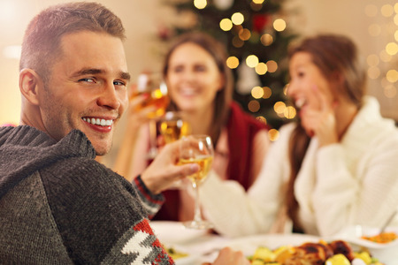 supper: Picture showing group of friends celebrating Christmas at home