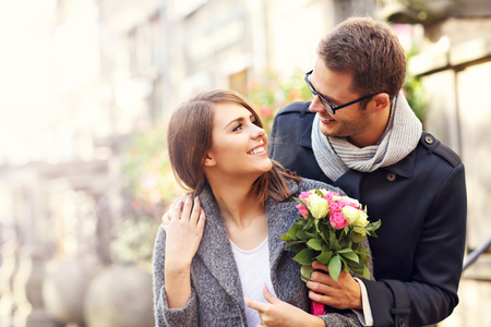couple dating: Picture showing young couple with flowers dating in the city