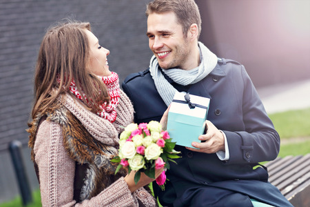 getting together: Picture showing young couple with present in the city