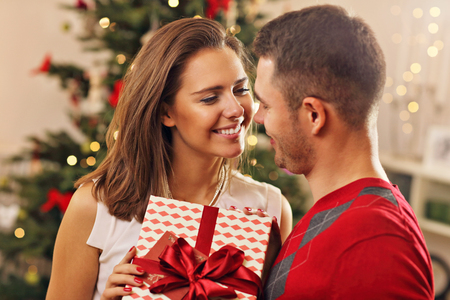 Picture showing young couple with present over Christmas tree