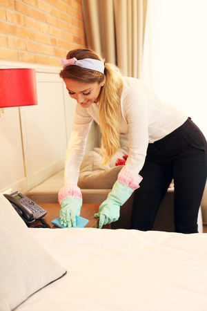 bed sheet: Picture of maid cleaning hotel room