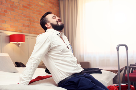 Picture showing tired businessman relaxing in hotel room
