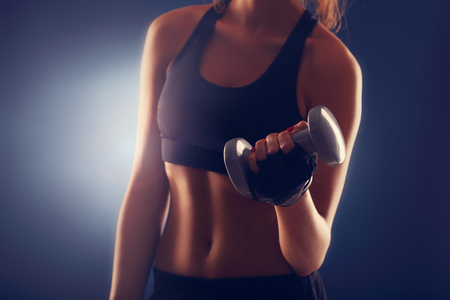 midsection: Midsection of woman lifting dumbells