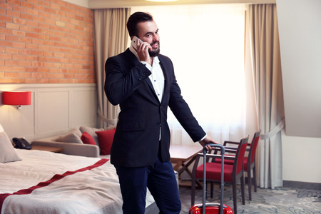 phone conversation: Picture showing young businessman in hotel room with smartphone