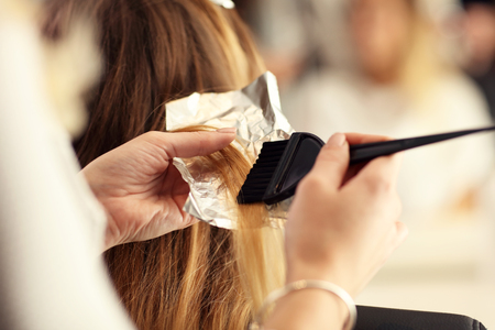 Picture showing hairdresser coloring hair in studio Stock Photo