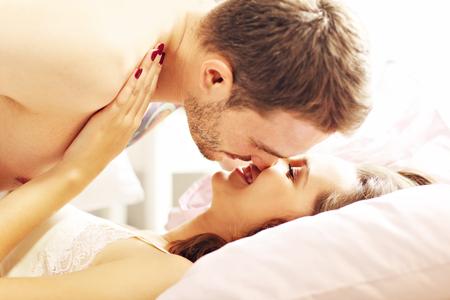 niño sin camisa: Imagen de la joven pareja besándose en la cama Foto de archivo