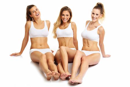 Grupo de amigos felices en ropa interior sobre fondo blanco