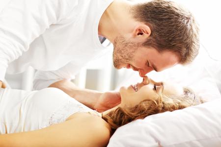 Beeld van jonge paar kussen in bed Stockfoto - 69020340