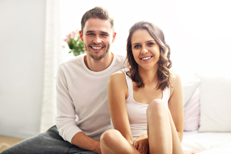 nightwear: Picture showing happy couple sitting on the bed in nightwear Stock Photo