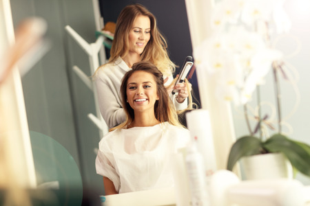 hair studio: Hairdresser using hair straightener in studio