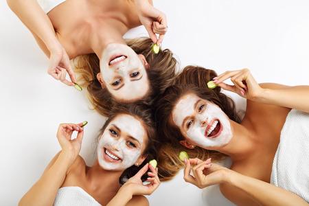 visage: Photo montrant trois amis avec des masques faciaux sur fond blanc