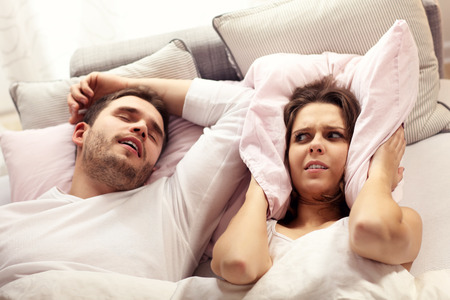 Picture of angry woman in bed with snoring man Stock Photo