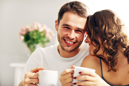 Picture of young couple drinking coffee in bed