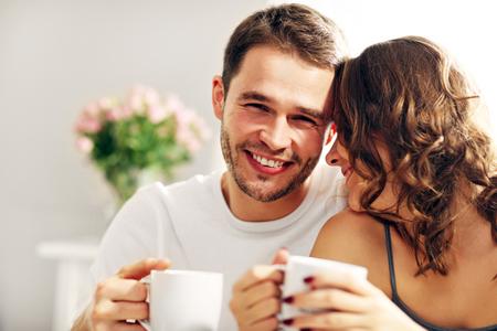 침대에서 커피를 마시는 젊은 부부의 사진