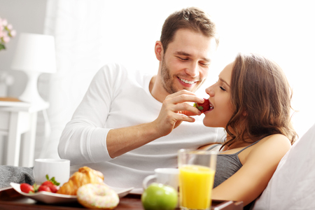 romantic room: Picture of young couple eating breakfast in bed