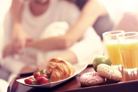desayuno romantico: Fotografía de una pareja joven que come el desayuno en la cama