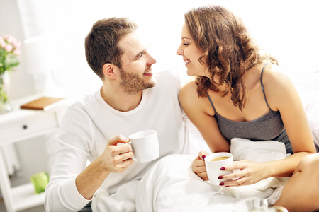 day bed: Picture of young couple drinking coffee in bed
